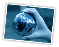 photo noir / blanc, filtre bleuté : une main tient un petit globe terrestre en métal.